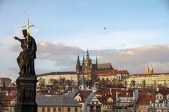 Charles Bridge Statue with shiny cross & St Vitus Cathedral. The roofs of Prague Castle are overlooked by the Gothic Spires of St Vitus Cathedral, while in the stock photo