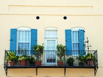 Charleston South Carolina Balcony Detail. A balcony on the Battery in Charleston, South Carolina with blue shutters, potted plants, a wrought iron railing, and a Royalty Free Stock Photo