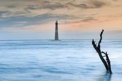 Charleston South Carolina Morris Island Lighthouse Sunrise. The defunct Morris Island Lighthouse at sunrise, an historical site north of Folly Beach near stock photography
