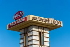English and Arabic Sign: Charley`s Philly Steaks sign on a blue sky background stock photography