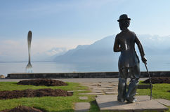 Charlie Chaplin and the Giant Fork. A bronze statue of Charlie Chaplin stares at the Giant Fork in Lake Geneva at Vevey where he lived and died Stock Images