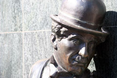 Charlie Chaplin statue. Bronze statue of actor Charlie Chaplin with bowler hat, wall in background Royalty Free Stock Photo