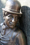 Charlie Chaplin statue. Bronze statue of Charlie Chaplin with traditional bowler hat, wall in background Stock Images