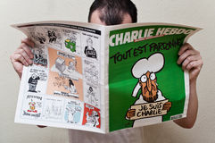 Charlie Hebdo magazine 14 January 2015 edition after the terrorism attack, on January 7th, 2015 in Paris. Man reading the Charlie Hebdo magazine the 14 January Royalty Free Stock Photos