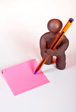 Charlie little. A little clay figure writing in a pink paper on white dektop Royalty Free Stock Images