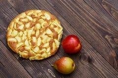 Charlotte de manzanas y de peras en un fondo de madera marrón Aún-vida del otoño Fotografía de archivo