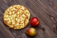 Charlotte des pommes et des poires sur un fond en bois brun Encore-durée d'automne Photographie stock
