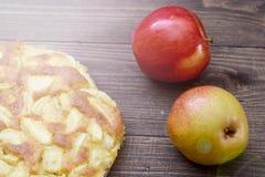 Charlotte des pommes et des poires sur un fond en bois brun Encore-durée d'automne Images stock
