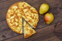 Charlotte des pommes et des poires sur un fond en bois brun Encore-durée d'automne Image libre de droits