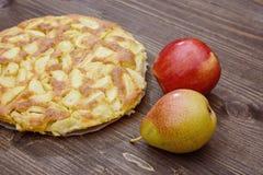 Charlotte des pommes et des poires sur un fond en bois brun Encore-durée d'automne Photo stock