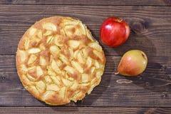 Charlotte des pommes et des poires sur un fond en bois brun Encore-durée d'automne Photos stock