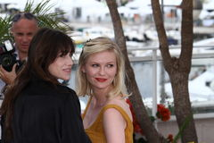 Charlotte Gainsbourg and Kirsten Dunst. CANNES, FRANCE - MAY 18: Charlotte Gainsbourg and Kirsten Dunst attend the 'Melancholia' photocall at the Palais des stock photos