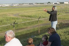 Woman prays for a departing plane at Charlotte Airport runway. royalty free stock image
