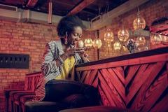 Charma afrikansk amerikankvinnlign som tycker om delightedly kaffesmak som är på stången arkivbilder