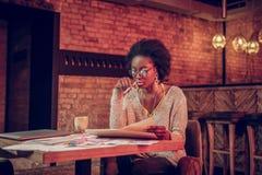 Charma Afro--amerikan den kvinnliga kontrollerande sketchbooken, medan sitta med kaffe arkivbilder