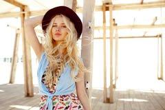Charma blondinen med lockigt hår, blåa ögon, stora kanter och burgundy hatt som isoleras på den träbyggande bakgrunden arkivbilder