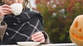 Charma damen som har koppen kaffe nära den sned stålar-nolla-lyktan, allhelgonaaftonhelgdagsafton stock video