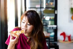 Charma den härliga asia kvinnan tyck om att äta smaskig pizza och klibbig mozzarellaost Det har bra smak Den nätta kundflickan få arkivfoton