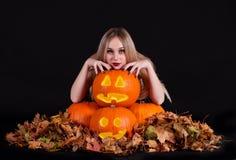 Charma den halloween häxan med glödande roliga pumpor och sidor Arkivfoto
