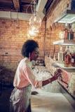 Charma den kvinnliga bärande vita skjortan som gör lokalvård i bar arkivbild