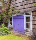 Charma den red ut trädgårds- stugan med en purpurfärgad trädörr Royaltyfri Bild