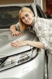 Charma den unga kvinnan som köper den nya bilen royaltyfri fotografi
