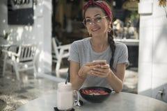 Charma den unga modellen med härligt leende genom att använda den moderna telefonen som läser goda nyheter fotografering för bildbyråer