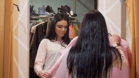 Charma försökande kläder för ung kvinna framme av en spegel på klädlagret stock video