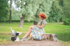 Charma flickan med rött hår i retro stil som poserar i en tappningklänning fotografering för bildbyråer