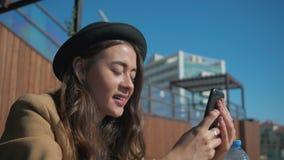 Charma flickan på socialt massmedia via den utomhus- smartphonen arkivfilmer