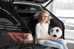 Charma flickan som sitter i bilstam av återförsäljarevisningslokalen royaltyfria foton