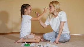 Charma flickor som sitter på golv med papper och vattenfärgen och till varandra som målar näsor har gyckel lager videofilmer
