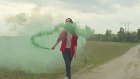 Charma kvinnan som går i färgrök bland fält