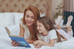 Charma kvinnan som l?ser en bok till hennes lilla dotter arkivfoton