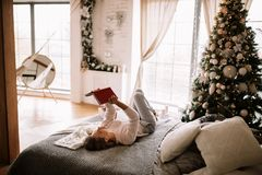 Charma tröjan och flåsanden för flicka den iklädda vita läser en bok som liying på sängen med den gråa filten, vita kuddar och a royaltyfria foton
