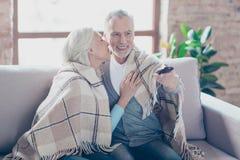 Charma två äldre personer sitter på en hemmastadd resti för soffa arkivbild