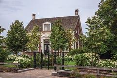 Charmant baksteen rustiek huis met gebloeide tuin en ijzerpoort in een bewolkte dag in Drimmelen royalty-vrije stock afbeeldingen