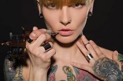 Charmant blonde met tatoegeringsmachine en voor hen Stock Afbeeldingen