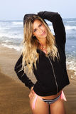 Charmant en zoet jong blondemeisje bij het overzees die zich met zwart sweatshirt bevinden Stock Afbeeldingen