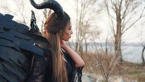 Charmant fantasiebeeld van femme fatale die dood en oorlog, engel van duisternis met grote vleugels en hoornen in lang brengt stock footage