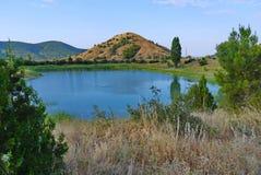 Charmant klein meer met duidelijk blauw die water op een schilderachtig gebied bij de voet van de heuvel wordt gevestigd stock afbeelding