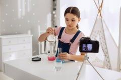 Charmant meisje die chemische producten en het registreren van het mengen Stock Foto's