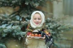 Charmant meisje die in Russisch chalet een plaat met paaseieren houden stock afbeeldingen