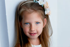 Charmant meisje met lang as-blond haar, levendige blauwe ogen en een geknepen neus, met de hand gemaakte vatting, stock fotografie