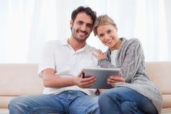 Charmant paar dat een tabletcomputer met behulp van Stock Foto