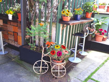 Charmant terras met bloemen en uitstekende cyclus stock foto