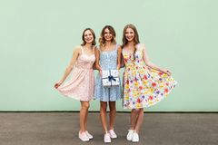 Charmant trois beaux jeunes amis adultes avec les robes et la boîte actuelle souriant et regardant l'appareil-photo Image libre de droits