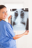 Charmante arts die en een röntgenstraal glimlacht houdt Royalty-vrije Stock Afbeeldingen