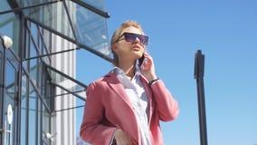 Charmante bedrijfsvrouw die met klanten in de straat spreken Lage hoekmening Modieus kijk stock videobeelden