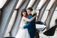 Charmante bruid en bruidegom die op hun huwelijksviering omhelzen in luxueus restaurant stock afbeelding